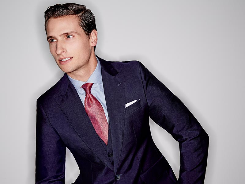 Head and shoulders shot of man wearing blue suit, red tie and white pocket sqaure