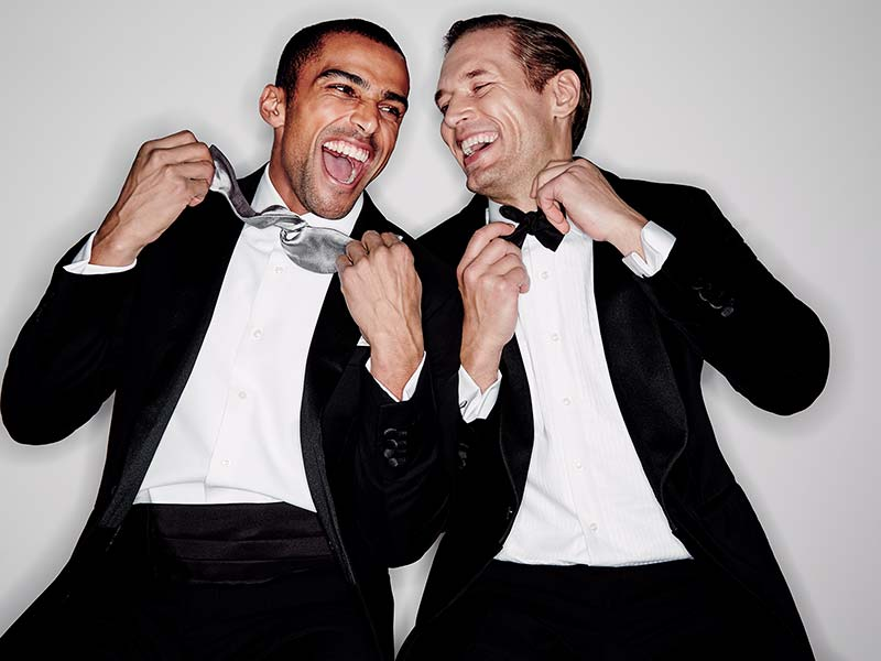 Two men laughing whilst tying their bow ties
