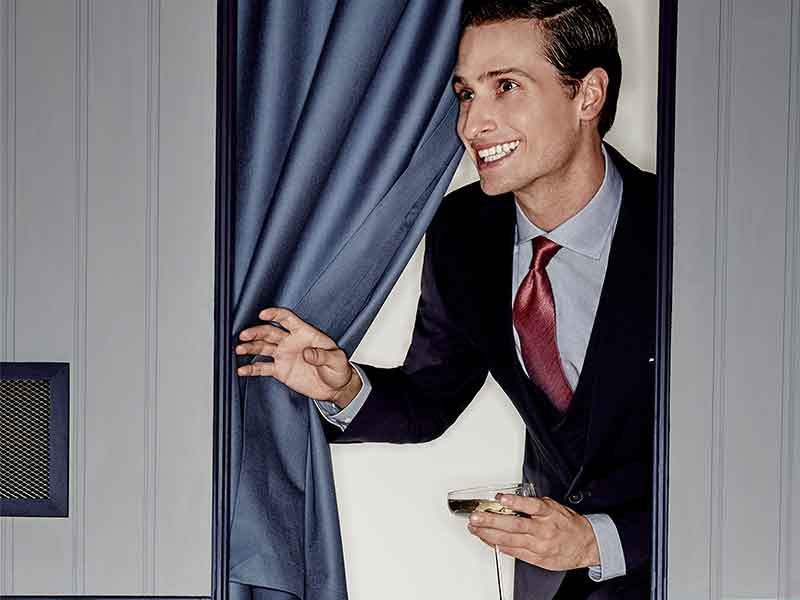 Man in suit smiling peering through photobooth with cocktail in hand