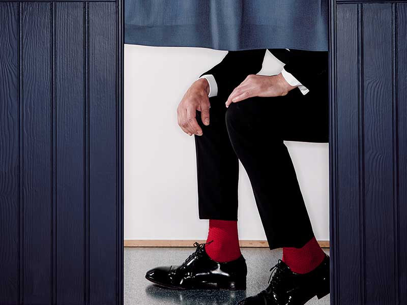 Close up shot of mens trouser, socks and shoes sat in wedding photobooth