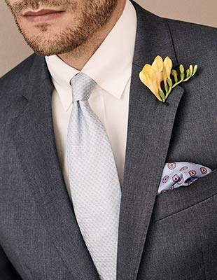 Man in suit with pockett square and pinhole wedding flower