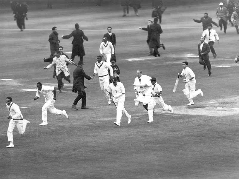 cricket players running across pitch