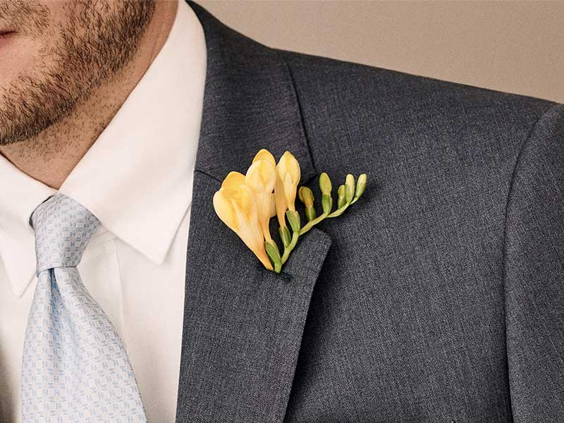 man in suit with button hole flower