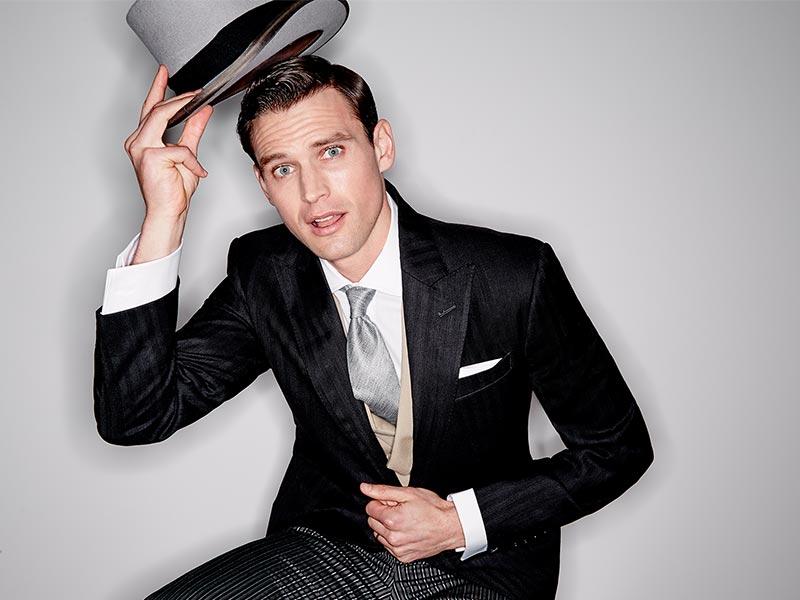 Man formal wedding attire tipping his top hat toward the camera