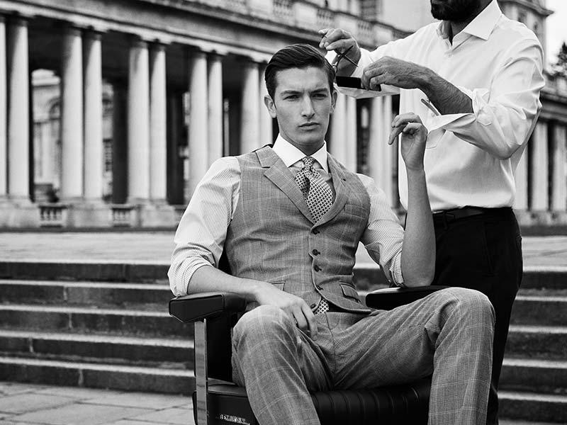 man in waistcoat having haircut